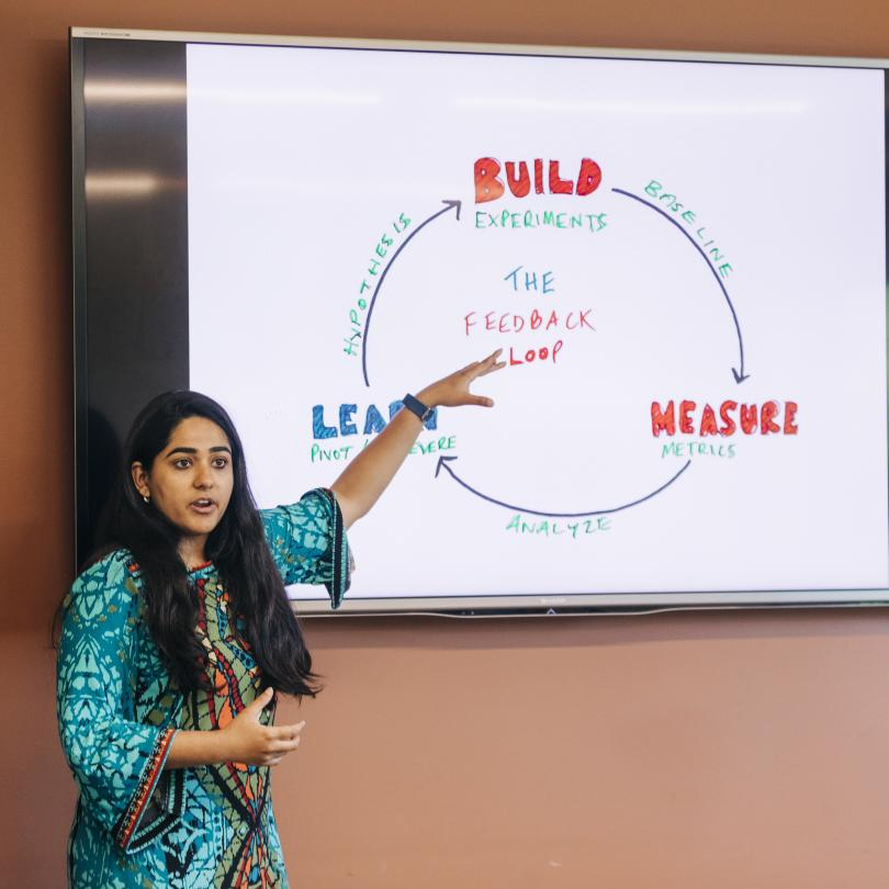 Mansi Kakkar pointing to a diagram with a circle explaining how businesses build, measure and learn